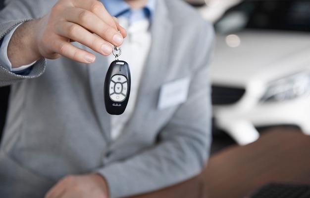 車のキーを持つ車のセールスマンの低いセクション