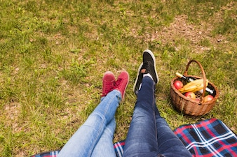 Low section of couple's leg on green grass with picnic basket