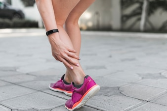 Low section of female athlete standing on street having pain in ankle