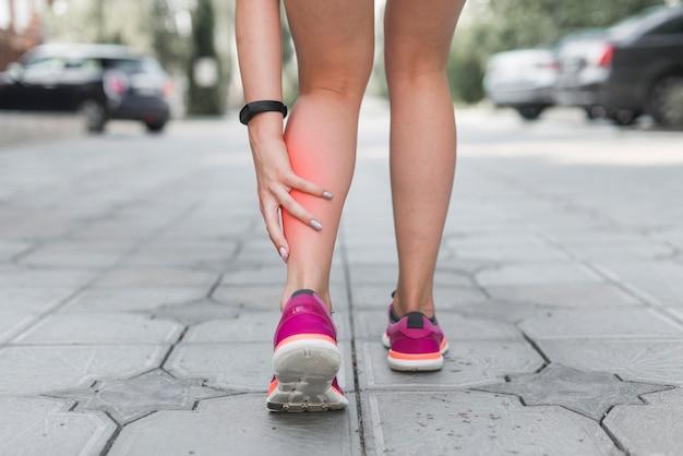 脚に痛みを伴う路上に立っている女性のアスリートの低い部分