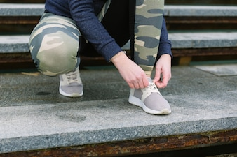 Low section of female jogger tying shoelace