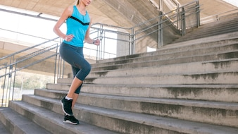 Low section of fitness young woman jogging on staircase