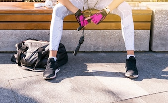 Low section of fitness young woman sitting on bench holding skipping rope in hand