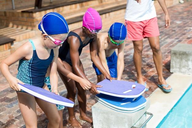 プールサイドでビート板を配置するために子供たちを支援するライフガードの低いセクション