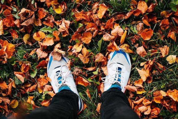 흰색 신발을 신은 남자의 낮은 부분은 가을 배경, 떨어진 주황색 잎이 있는 녹색 잔디, 위쪽 전망에 서 있습니다. 안녕하세요 10 월 개념