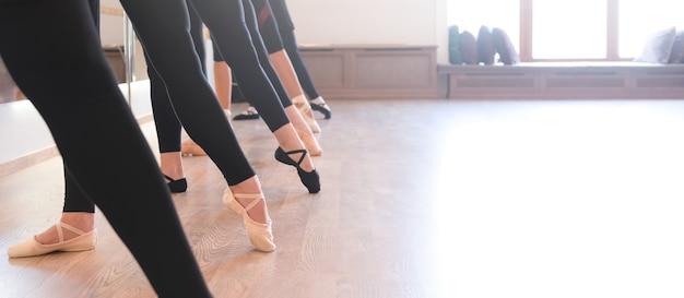 발끝으로 일렬로 서 있는 발레 댄서들의 우아한 다리의 낮은 부분