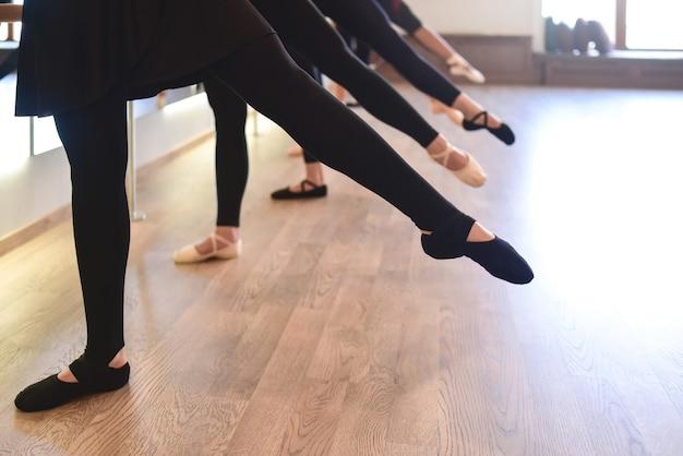 일렬로 서 있는 발레 댄서들의 우아한 다리의 낮은 부분은 스트레칭 운동을 한다