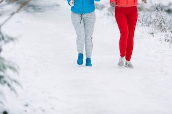 Low section of two female friends walking on frozen landscape
