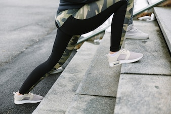 Low section of two female joggers stretching on staircase