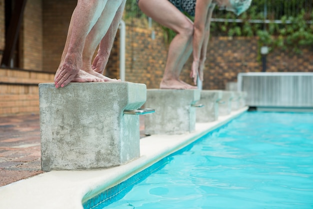 プールでダイビングする準備をしている2人の年配の女性の低いセクション