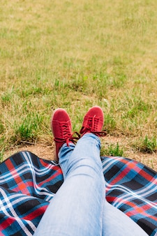 Low section of woman's crossed leg wearing red shoes on blanket