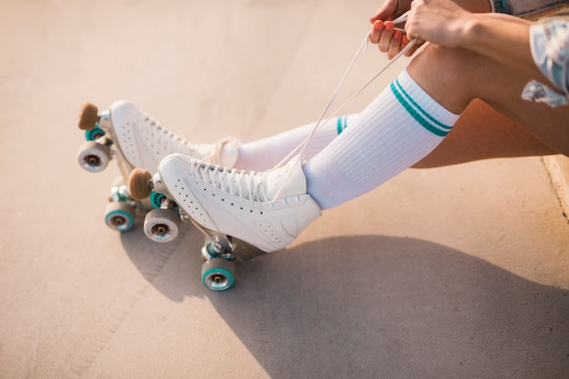 Низкая часть женщины, завязывающая шнурок на роликах