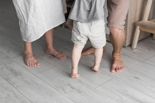 Low section of parent with their little son standing on hardwood floor
