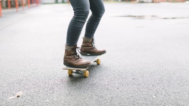 Low section of skateboarder riding skateboard