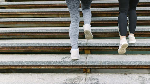 Low section of two female runner jogging on staircases