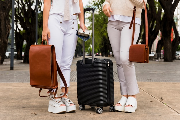 Low section of two young women standing with black suitcase and their leather bags