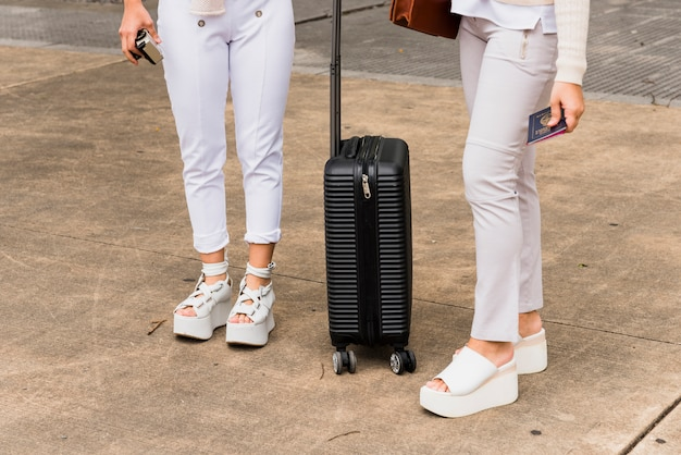Low section of two young women standing with black suitcase