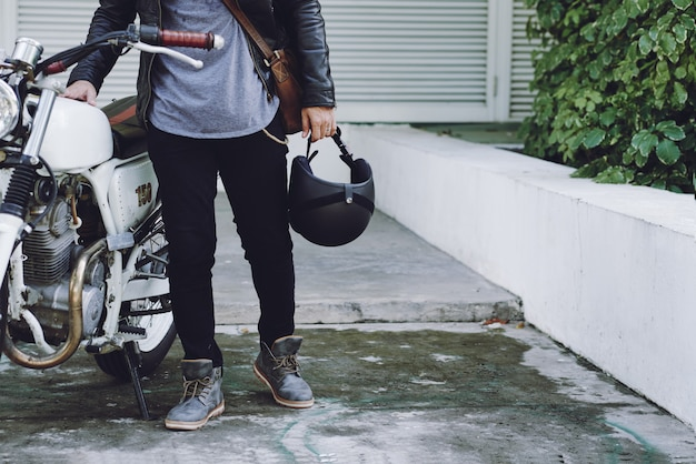 Low section of unrecognizable biker holding helmet standing at his white motorbike