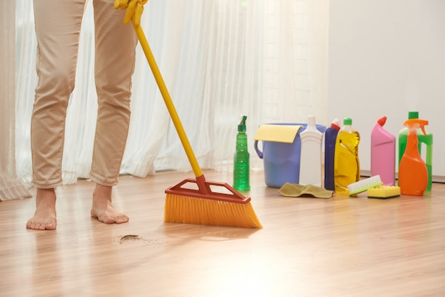 Low section of unrecognizable woman sweeping floor with broom
