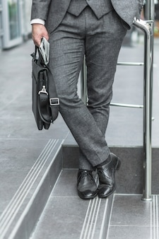 Low section view of a businessman holding shoulder bag