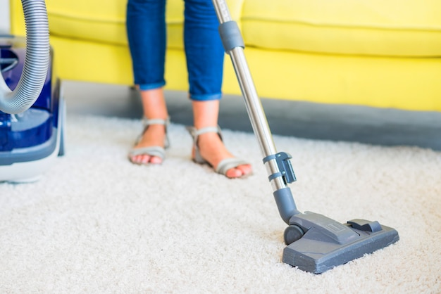 Low section view of a female janitor cleaning carpet with vacuum cleaner