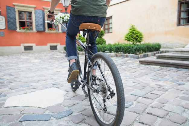 Low section view of a man riding bicycle