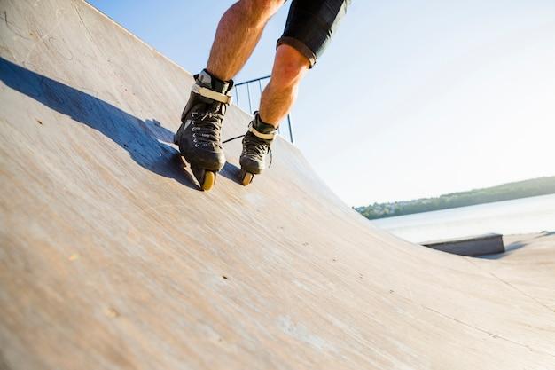Vista in sezione bassa di un uomo che pattina nel parco skate