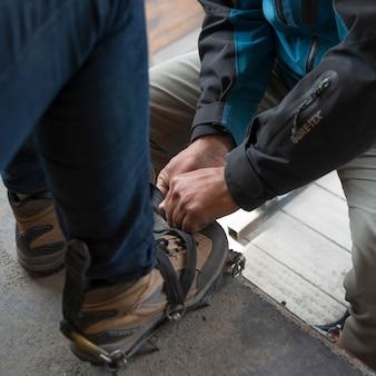 Low section view of men putting on crampon boot, perito moreno glacier, santa cruz province, patagon