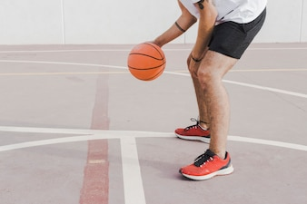 Low section view of a man practicing basketball in court