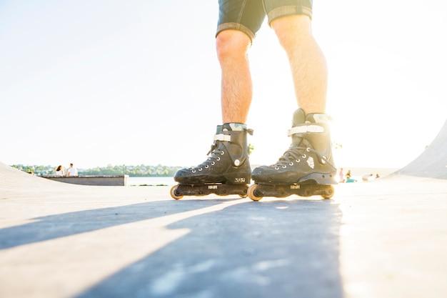 Низкий разрез мужчины, который катается на роликах в скейт-парке летом
