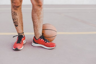 Low section view of a man's feet with basketball
