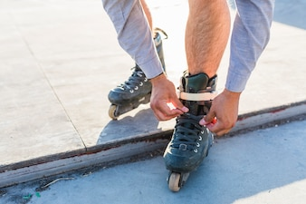 Low section view of man putting on rollerskates