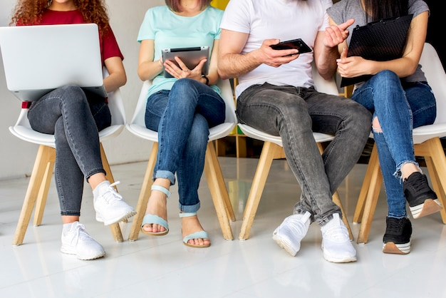 Low section view of people sitting on chair using wireless devices