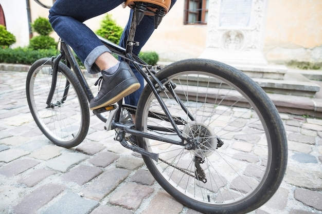 Low section view of a person's feet riding bicycle at outdoors