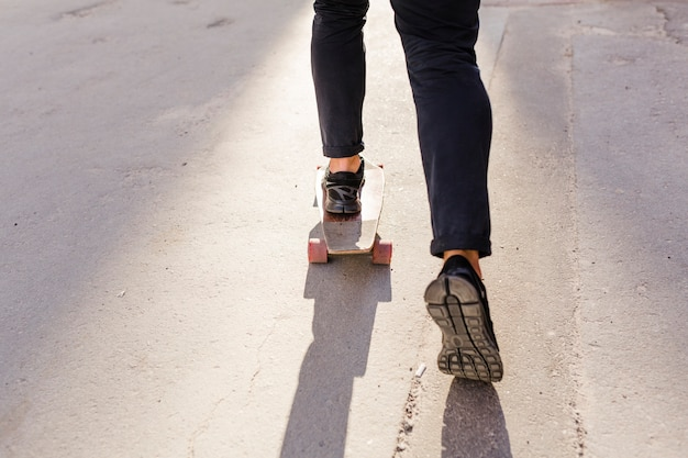 Low section view of a person's feet skating on wooden skateboard