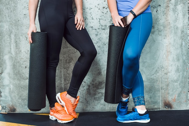 Low section view of two women with exercise mat in gym