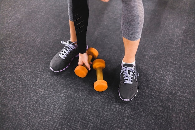 Low section view of a woman picking dumbbell in gym