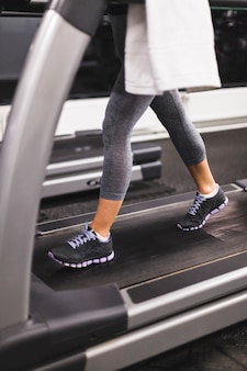 Low section view of a woman running on treadmill