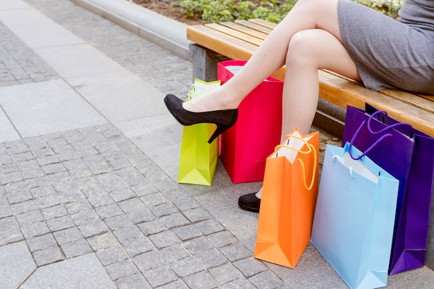 Low section view of a woman's leg with multi colored shopping bags