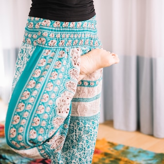 Low section of woman doing yoga practice at home