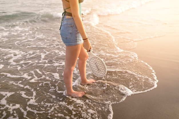 Low section of woman holding racket in hand standing barefoot at seacoast