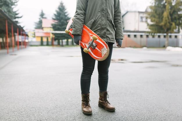 Low section of woman holding skateboard in hand