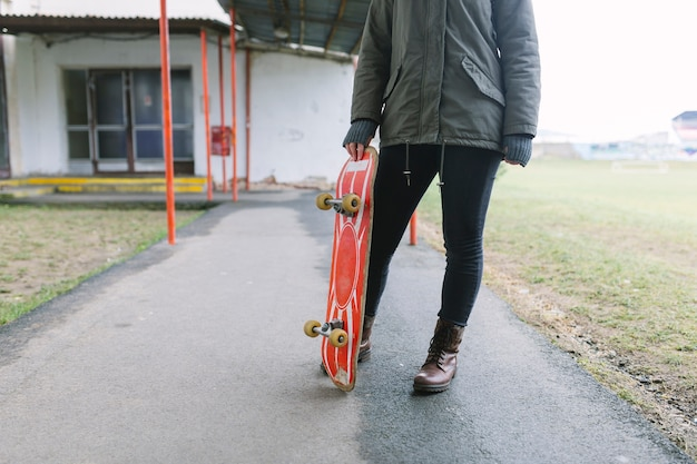 Low section of a woman holding skateboard on walkway