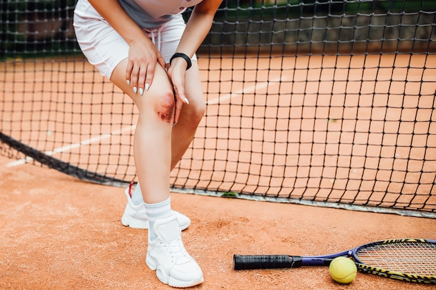 Low section of  woman holding tennis racket while suffering from knee pain on red tennis court during summer.