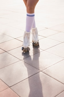 Low section of woman in roller skate standing with crossed legs on floor