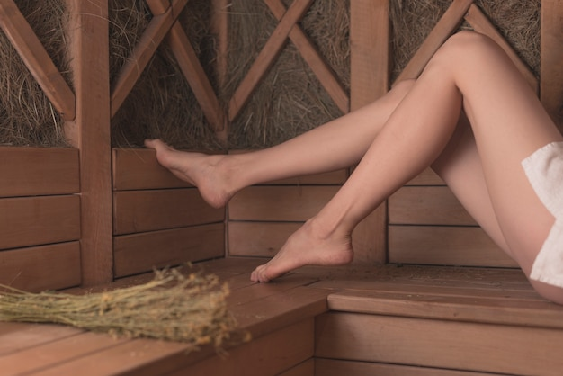Low section of woman's feet on wooden bench in sauna
