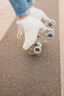 Low section of woman's foot wearing white roller skate balancing on road
