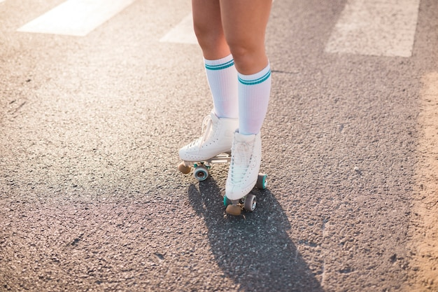 Low section of a woman wearing roller skate standing on asphalt