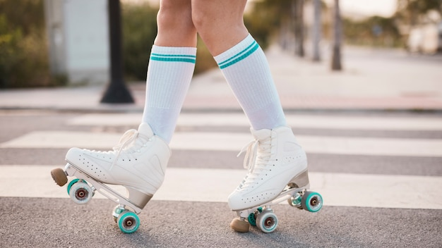 Low section of woman wearing vintage roller skate walking on road