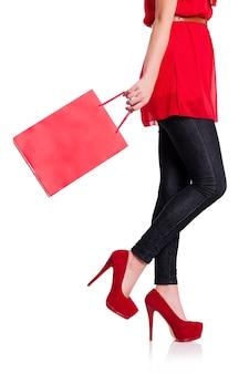 Sezione bassa di una donna con la sua borsa della spesa rossa